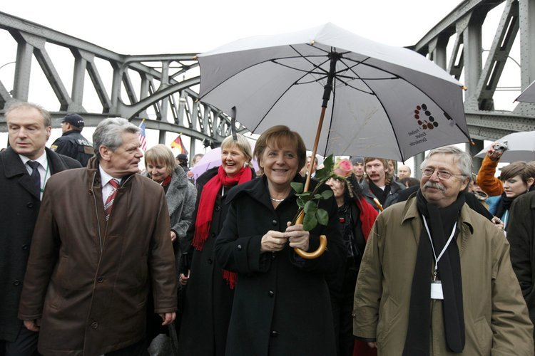 German Chancellor Merkel walks through the Bornholmer Bridge (Bruecke) with people who crossed it first twenty years ago, in Berlin
